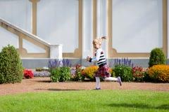 使用在夏天绿色公园的快乐的矮小的白肤金发的女孩 库存照片