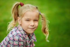 使用在夏天绿色公园的小俏丽的女孩画象  免版税库存照片
