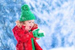 使用在多雪的公园的小女孩 免版税图库摄影