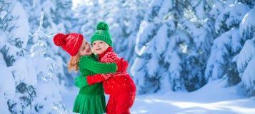 使用在多雪的冬天森林里的孩子 免版税库存照片