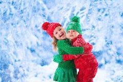 使用在多雪的冬天森林里的孩子 免版税库存图片