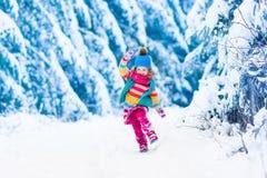 使用在多雪的冬天森林里的小女孩 免版税库存照片