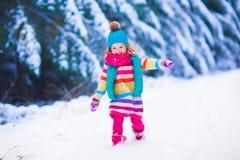 使用在多雪的冬天森林里的小女孩 库存图片