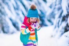 使用在多雪的冬天森林里的小女孩 免版税库存图片
