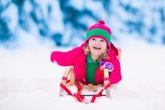 使用在多雪的冬天森林里的小女孩 免版税图库摄影