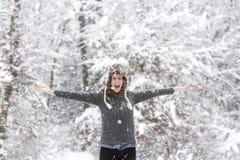 使用在多雪的森林的激动的少妇 免版税库存图片