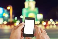 使用在夜街道上的妇女巧妙的电话 免版税库存照片