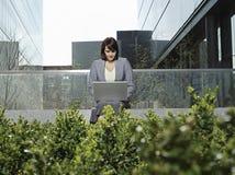 使用在大厦之外的女实业家膝上型计算机 免版税库存图片