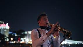使用在大城市的夜散步的萨克斯管吹奏者 一位街道音乐家的表现在观众前面的 影视素材