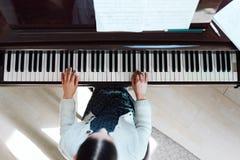 使用在大平台钢琴,顶视图的女孩 免版税库存照片