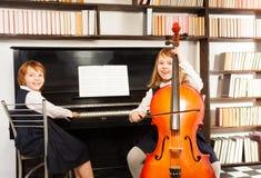 使用在大提琴和钢琴的礼服的女孩 库存图片