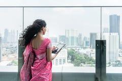 使用在大阳台的年轻印地安妇女一台片剂个人计算机在一个大风天 免版税库存照片