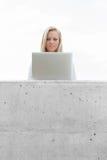 使用在大阳台的年轻女实业家膝上型计算机反对天空 库存照片