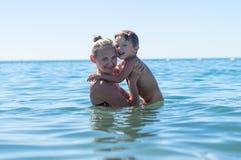 使用在天时间的海滩的母亲和儿子 愉快的小孩男孩画象海滩的海洋 滑稽的逗人喜爱的儿童maki 免版税图库摄影