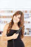 使用在她光亮的头发的美丽的女孩styler 免版税库存照片