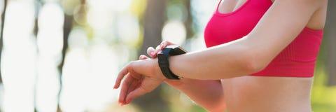 使用在她巧妙的手表的可爱的运动员健身app监测锻炼表现 万维网横幅 免版税库存照片