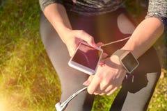使用在她巧妙的手表的女运动员健身app监测锻炼表现 生活方式便携的技术概念 免版税库存照片