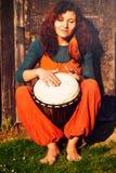 使用在她的在土气木门背景的djembe鼓的年轻人赤足夫人鼓手 库存图片