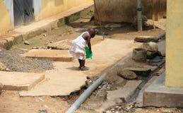 使用在她的房子前面的可怜的非洲女孩 免版税库存图片