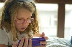 使用在她的手机的女孩在床上 免版税库存图片
