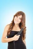 使用在她的头发的少妇卷曲铁 免版税库存图片