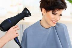 使用在妇女湿头发的美发师烘干机在沙龙。短发。 免版税库存照片