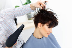 使用在妇女湿头发的美发师烘干机在沙龙。短发 免版税库存照片