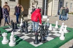 使用在委员会的巨大的移动的棋子的两个孩子在主要市场上在利沃夫州,人们摆正在他们附近注视着t 库存图片