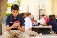 使用在学校校园里的男性高中学生电话 免版税库存图片