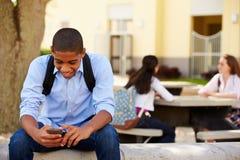 使用在学校校园里的男性高中学生电话 库存照片