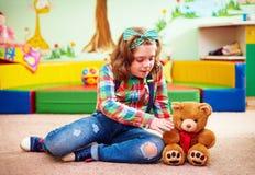 使用在孩子的幼儿园的逗人喜爱的女孩与特别需要 免版税库存照片