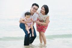 使用在室外沙子海滩的愉快的亚洲家庭 免版税库存照片