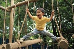 使用在室外障碍桩的日本男孩 库存照片