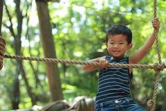 使用在室外障碍桩的日本男孩 免版税库存照片