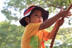 使用在室外障碍桩的日本男孩 库存图片