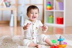 使用在家与五颜六色的玩具的逗人喜爱的女孩婴孩 免版税库存图片