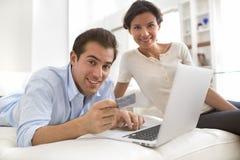 使用在家在网上购物的信用卡的夫妇 图库摄影