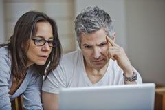 使用膝上型计算机的夫妇在家 库存图片