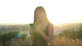 使用在小山时的电话认为年轻愉快的亚裔旅游的妇女,当 影视素材