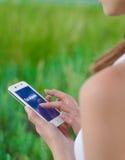 使用在巧妙的电话的少妇Facebook社会网络应用 图库摄影