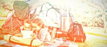 使用在帐篷之外的兄弟姐妹膝上型计算机在露营地 图库摄影