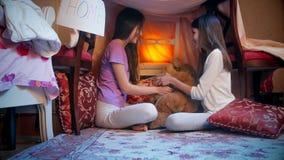 使用在帐篷的愉快的微笑的女孩由毯子制成在卧室 免版税库存图片