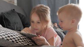使用在平板电脑的十几岁的女孩在家基于沙发 人、技术和休闲概念 影视素材