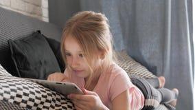 使用在平板电脑的十几岁的女孩在家基于沙发 人、技术和休闲概念 股票视频