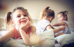 使用在床上的三个小女孩 图库摄影