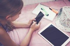 使用在床上的女孩智能手机 免版税图库摄影