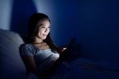 使用在床上的妇女手机在晚上 免版税库存图片