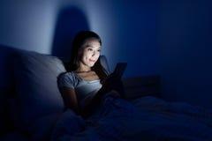 使用在床上的妇女手机在晚上 免版税库存照片