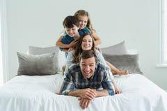 使用在床上的微笑的家庭画象在卧室 图库摄影