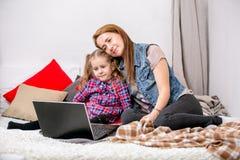 使用在床上的母亲和女儿膝上型计算机在卧室 母亲拥抱她的有爱和关心的女儿,并且他们微笑,当看t时 免版税库存图片